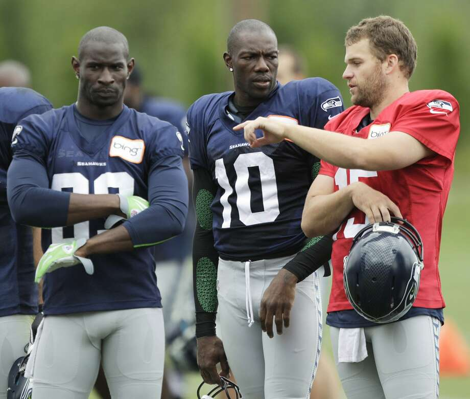 Seattle Seahawks wide receiver Terrell Owens, center, talks with Seahawks quarterback Matt Flynn, right, as wide receiver Ricardo Lockette, left, listens during NFL football training camp, Wednesday, Aug. 8, 2012, in Renton, Wash. (Ted S. Warren / Associated Press)