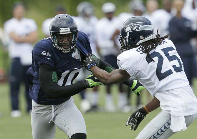 Seattle Seahawks' Terrell Owens (10) tangles with Richard Sherman, right, as they look for a pass during NFL football training camp, Wednesday, Aug. 8, 2012, in Renton, Wash. (Ted S. Warren / Associated Press)