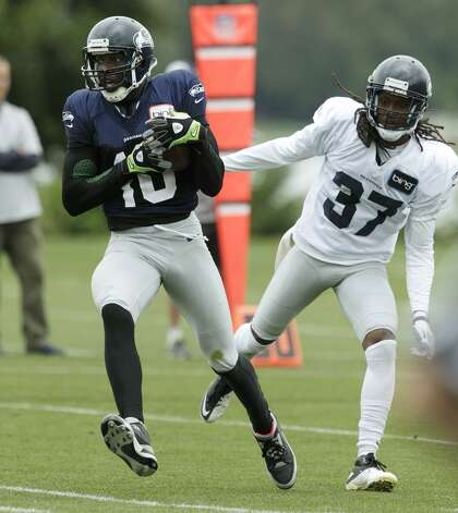 Seattle Seahawks' Terrell Owens, left, makes a catch around the defense of Seahawks' cornerback Coye Francies (37) during NFL football training camp, Wednesday, Aug. 8, 2012, in Renton, Wash. (Ted S. Warren / Associated Press)