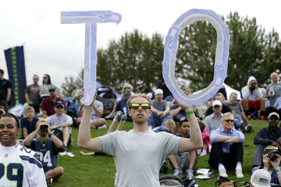 Seattle Seahawks fan Aaron Fox, of Seattle, holds up a sign in support of Terrell Owens' first day of NFL football training camp with the Seahawks, Wednesday, Aug. 8, 2012, in Renton, Wash. (Ted S. Warren / Associated Press)
