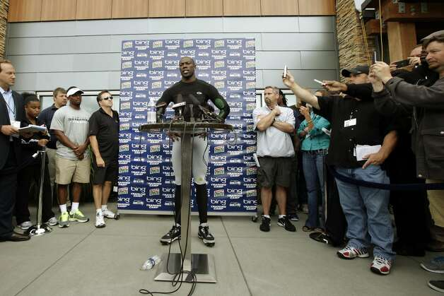 Seattle Seahawks wide receiver Terrell Owens, center, talks to reporters following his first day with the Seahawks at NFL football training camp, Wednesday, Aug. 8, 2012, in Renton, Wash. (Ted S. Warren / Associated Press)