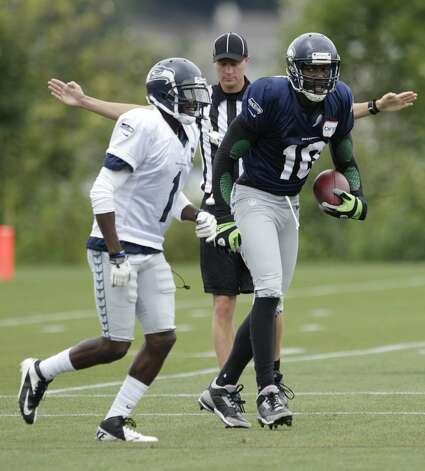 Seattle Seahawks wide receiver Terrell Owens, right, looks at cornerback Jeremy Lane, left, after a play during NFL football training camp, Wednesday, Aug. 8, 2012, in Renton, Wash. (Ted S. Warren / Associated Press)