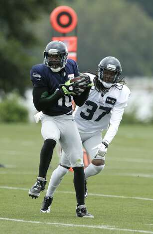 Seattle Seahawks' Terrell Owens (10) makes a catch over the defense of Coye Francies (37) during NFL football training camp, Wednesday, Aug. 8, 2012, in Renton, Wash. (Ted S. Warren / Associated Press)