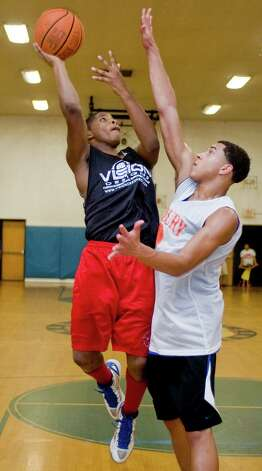 Abbott Tech's Dominique Rogers is guarded by Danbury High School's Javonte Parker in the championship game of the War Memorial Summer High School Basketball League. Wednesday, Aug. 8, 2012 Photo: Scott Mullin / The News-Times Freelance