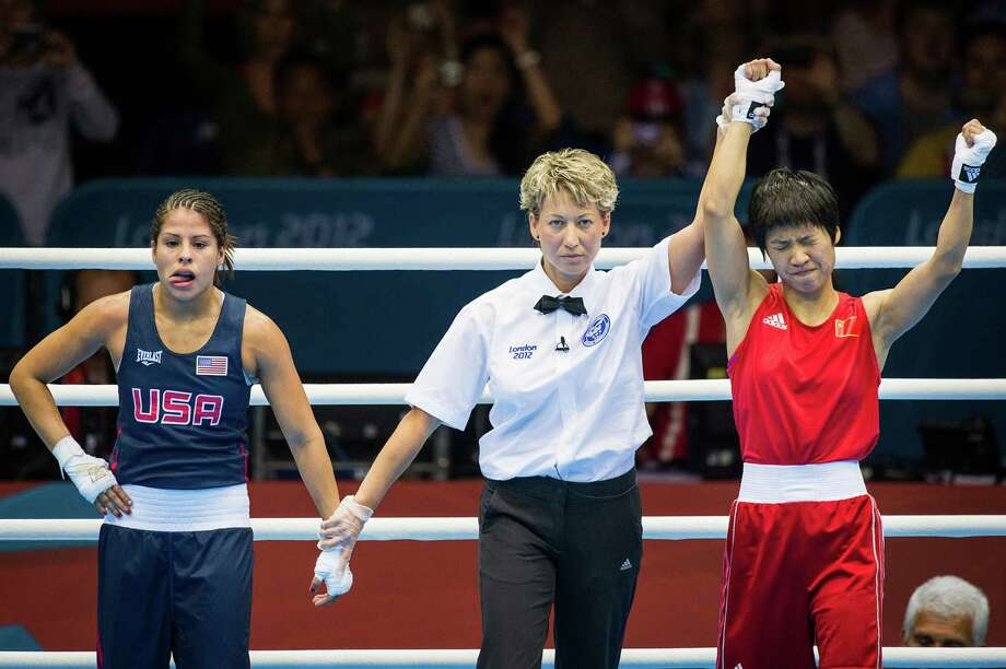 Marlen Esparza of the USA, in blue, reacts as referee Veronika Szucs raises the hand of her opponent to signify a victory by Ren Cancan of China in women's semifinal flyweight 51-kg boxing match at the 2012 London Olympics on Wednesday, Aug. 8, 2012. Photo: Smiley N. Pool, Houston Chronicle / © 2012  Houston Chronicle