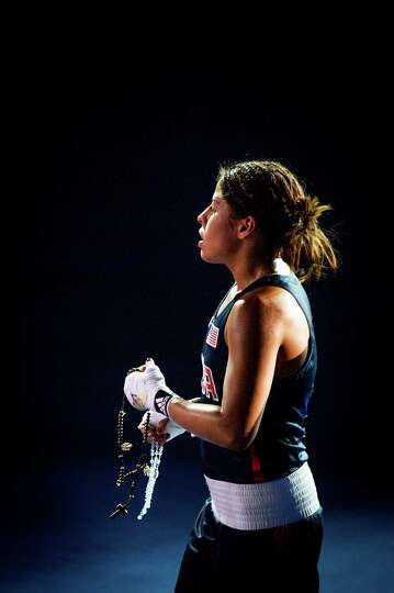 Marlen Esparza of the USA, clutches rosary beads as she leaves the ring after a loss to Ren Cancan o