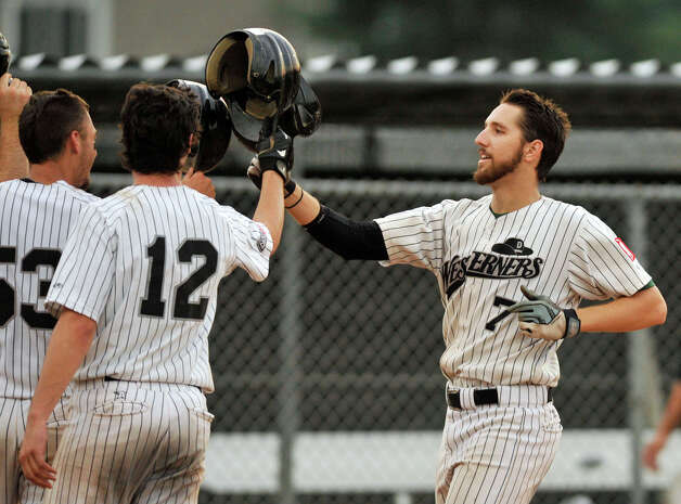 Andrew Garner, right, celebrates with teammates after hitting a grand slam during game 2 of their Western Division playoff game against Keene at Rogers Park in Danbury on Wednesday, Aug. 8, 2012. Danbury won, 12-11, advancing to the finals against the Newport Gulls. Photo: Jason Rearick / The News-Times
