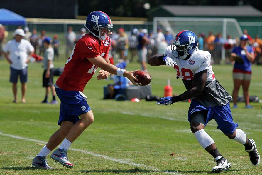 New York Giants quarterback #10 Eli Manning hands the ball of to runningback #28 D.J. Ware during th