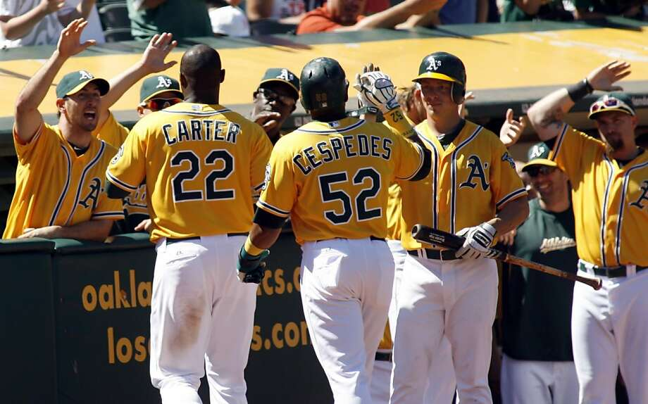 Oakland Athletics Chris Carter (22) is greeted by teammates after he hit a two-run home run, driving in Yoenis Cespedes, in the sixth inning of a baseball game in Oakland, Calif., Wednesday, Aug. 8, 2012. (AP Photo/Dino Vournas) Photo: Dino Vournas, Associated Press