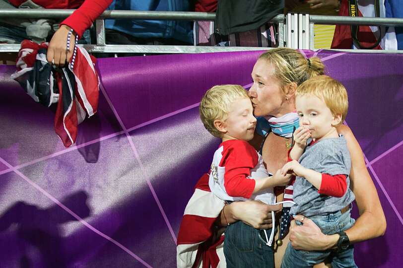 Kerri Walsh Jennings holds her sons Joey and Sundance as she celebrates after she and her partner Mi