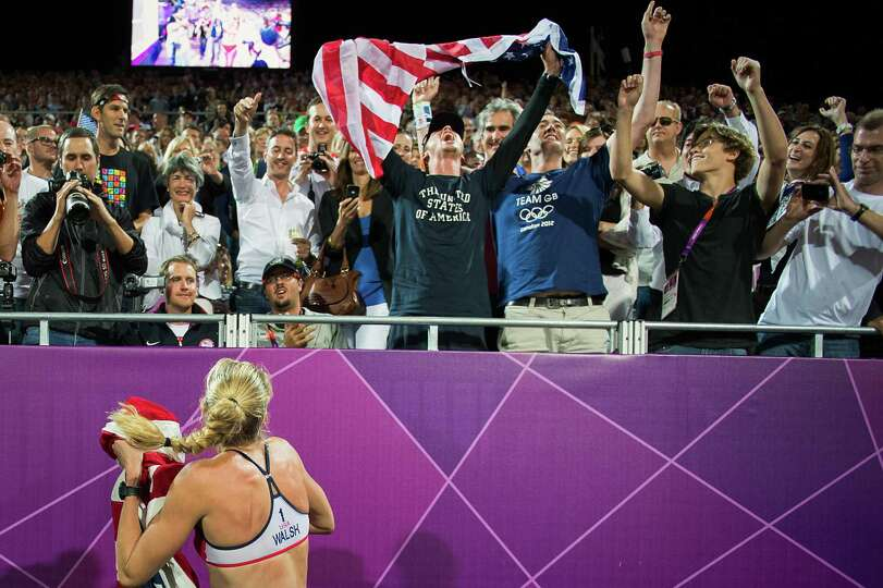 Kerri Walsh Jennings celebrates with the crowd after she and her partner Misty May-Treanor defeated
