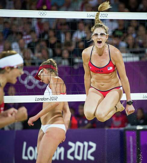 Kerri Walsh Jennings leaps in celebration after reaching match point with her partner Misty May-Trea