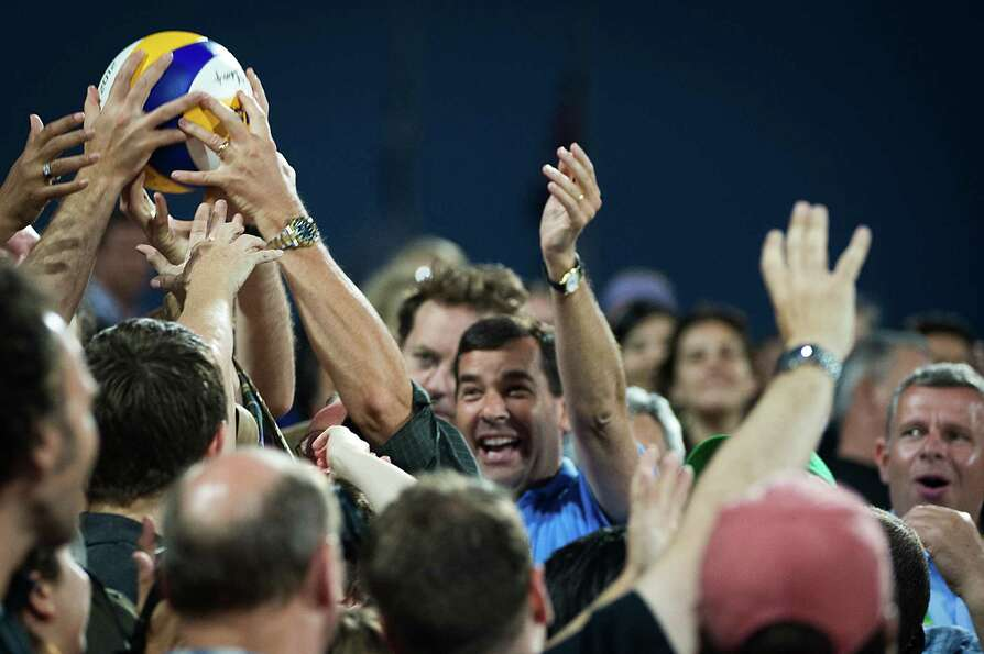 Fans reach for a ball thrown into the stands during the women's beach volleyball gold medal match.