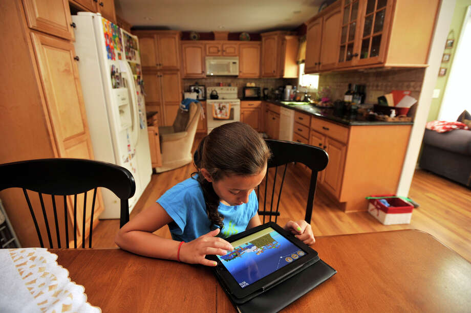 Kayla Mingachos, 10, plays on her new iPad 2 at her home in Danbury on Wednesday, Aug. 8, 2012. Kayla will be entering sixth grade at St. Gregory the Great School, which is requiring all students in sixth, seventh and eighth grade to purchase an iPad to use in most school-related activities. Photo: Jason Rearick / The News-Times