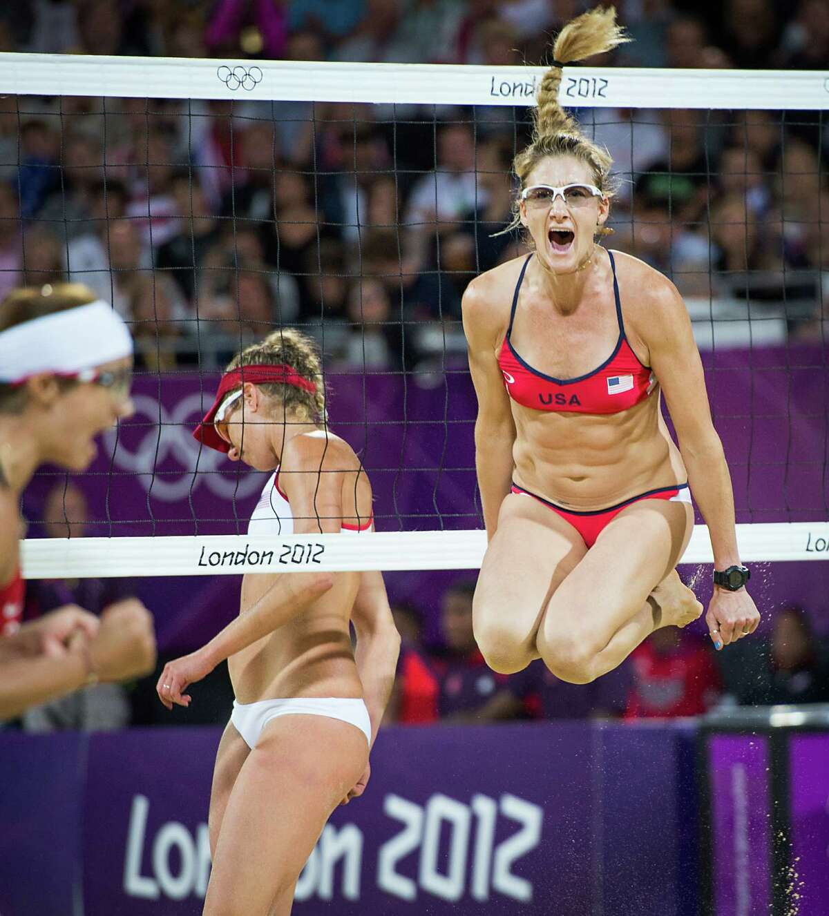 Kerri Walsh Jennings leaps in celebration after reaching match point with her partner Misty May-Treanor, left, on their way to defeating Jennifer Kessy and April Ross in the women's beach volleyball gold medal match at the 2012 London Olympics on Wednesday, Aug. 8, 2012.( Smiley N. Pool / Houston Chronicle )