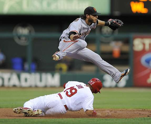San Francisco Giants shortstop Brandon Crawford leaps over St. Louis Cardinals' Jon Jay (19) as he turns a double play during the first inning of a baseball game Wednesday, Aug. 8, 2012, in St. Louis. Matt Carpenter was out at first. (AP Photo/Jeff Curry) Photo: Jeff Curry, Associated Press