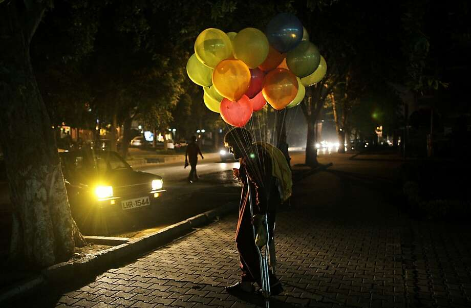 Pakistani vendor Sayed Anwar, 36, stands on a roadside hoping to sell balloons, in Islamabad, Pakistan, Wednesday, Aug. 8, 2012. Photo: Muhammed Muheisen, Associated Press