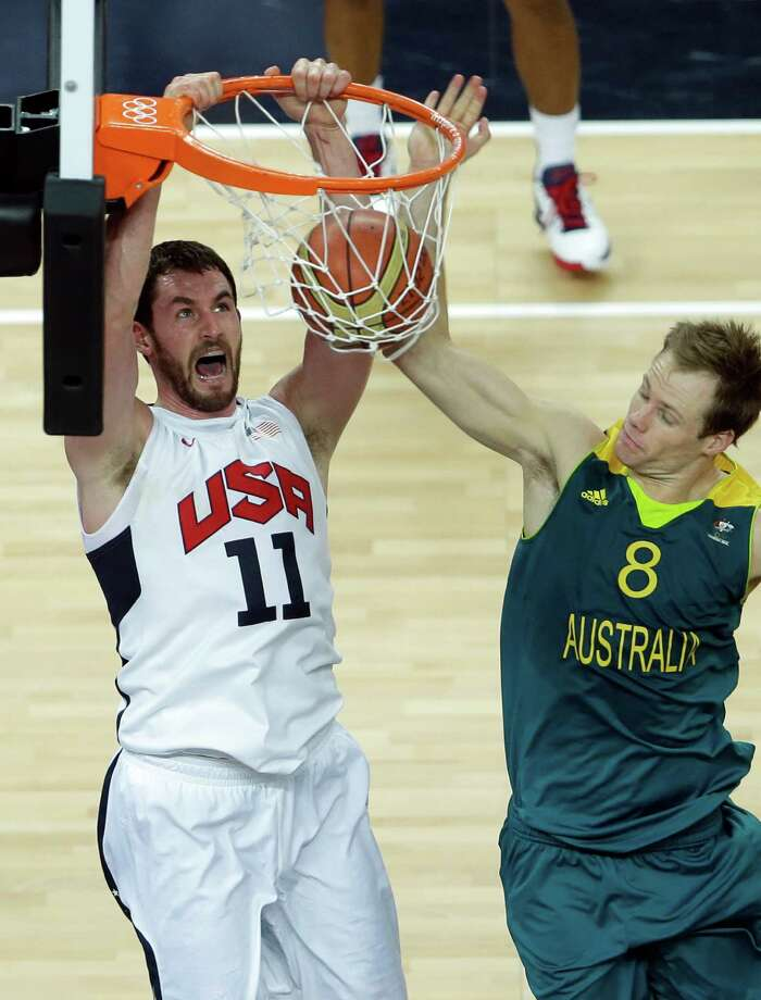 United States' Kevin Love, left, slams a dunk as Australia's Brad Newley, right, defends during a quarterfinal men's basketball game at the 2012 Summer Olympics, Wednesday, Aug. 8, 2012, in London. (AP Photo/Victor R. Caivano) Photo: Victor R. Caivano, Associated Press / AP