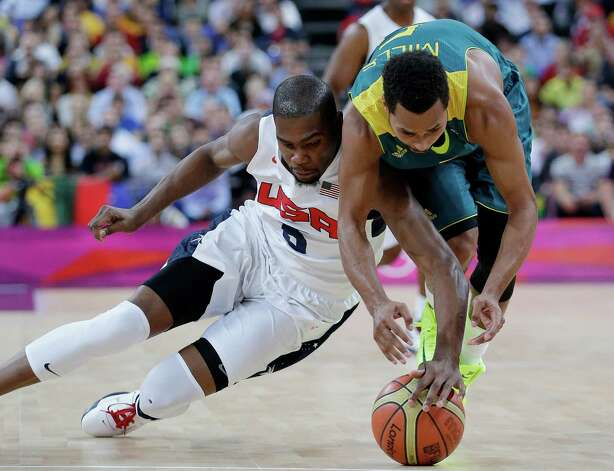 USA's Kevin Durant, left, and Australia's Patrick Mills, right, scramble for a loose ball during a quarterfinal men's basketball game at the 2012 Summer Olympics, Wednesday, Aug. 8, 2012, in London. (AP Photo/Eric Gay) Photo: Eric Gay, Associated Press / AP