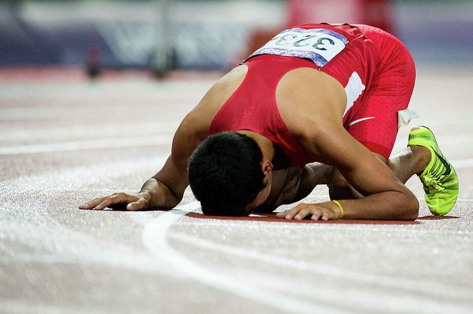 Leo Manzano of the USA kneels on the track after winning the silver with a time of 3:34.79 in the men's 1,500-meters final during at the 2012 London Olympics on Tuesday, Aug. 7, 2012.  It was the first medal won by the USA in the event in 44 years.  The last medal was won by Jim Ryun took the silver at the Mexico City Games in 1968.  Manzano is a former Texas Longhorn from Marble Falls. Photo: Smiley N. Pool, Houston Chronicle / © 2012  Houston Chronicle