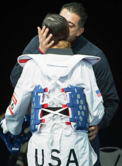 Diana Lopez of the USA gets a kiss from her coach, and brother, Jean Lopez before fighting Hou Yuzhu