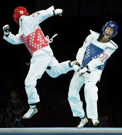 Diana Lopez of the USA, right, fights Hou Yuzhuo of China during a women's -57kg preliminary round taekwondo bout at the 2012 London Olympics on Thursday, Aug. 9, 2012. Lopez lost to the two-time world champion 1-0 in sudden death. Photo: Smiley N. Pool, Houston Chronicle / © 2012  Houston Chronicle