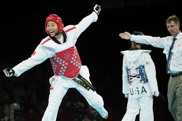 Hou Yuzhuo of China celebrates as she is awarded a point in sudden death to defeat Diana Lopez of the USA, background, in a women's -57kg preliminary round taekwondo bout at the 2012 London Olympics on Thursday, Aug. 9, 2012. Photo: Smiley N. Pool, Houston Chronicle / © 2012  Houston Chronicle