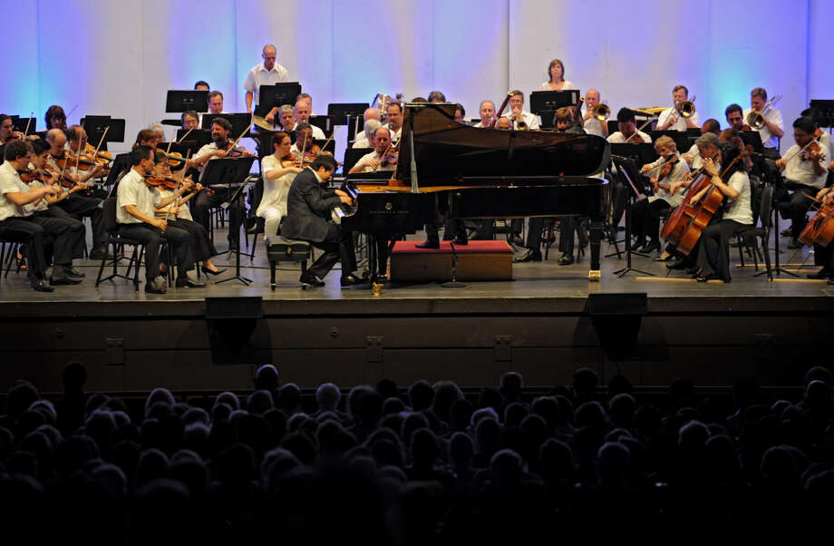 Music director Yannick Nezet-Seguin conducts the Philadelphia Orchestra with pianist Lang Lang on the piano at Saratoga Performing Arts Center Wednesday, Aug. 8, 2012 in Saratoga Springs, N.Y. This is Yannick Nezet-Seguin's first performance at SPAC. (Lori Van Buren / Times Union) Photo: Lori Van Buren