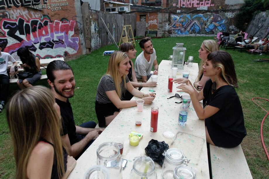 In this Wednesday, July 25 2012 photo, a group of people hang out at a picnic table at Timeshare Backyard on the Lower East Side of Manhattan. The city's lone timeshare backyard allows New Yorkers to invite up to 30 guests for two hours at a time and comes with grills, lounge chairs and trashy magazines. Photo: Mary Altaffer, AP / AP