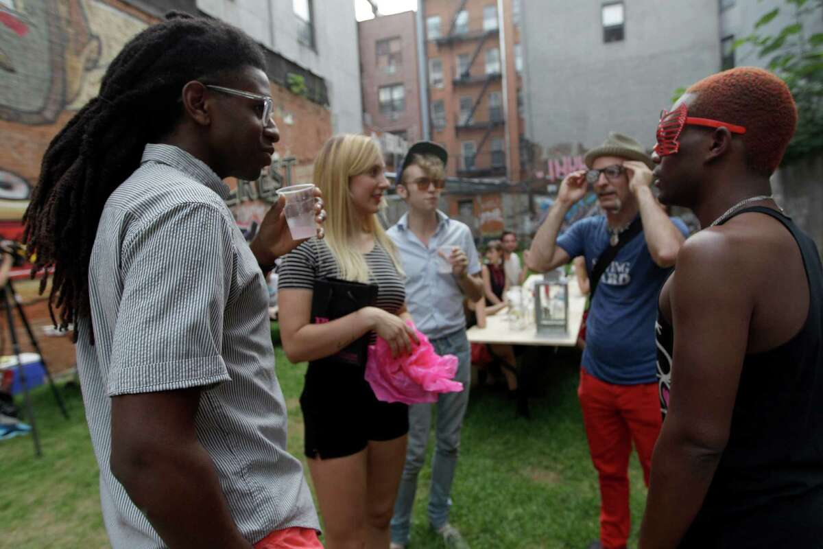 In this Wednesday, July 25 2012 photo, a group of people hang at Timeshare Backyard on the Lower East Side of Manhattan. The city's lone timeshare backyard allows New Yorkers to invite up to 30 guests for two hours at a time and comes with grills, lounge chairs and trashy magazines.