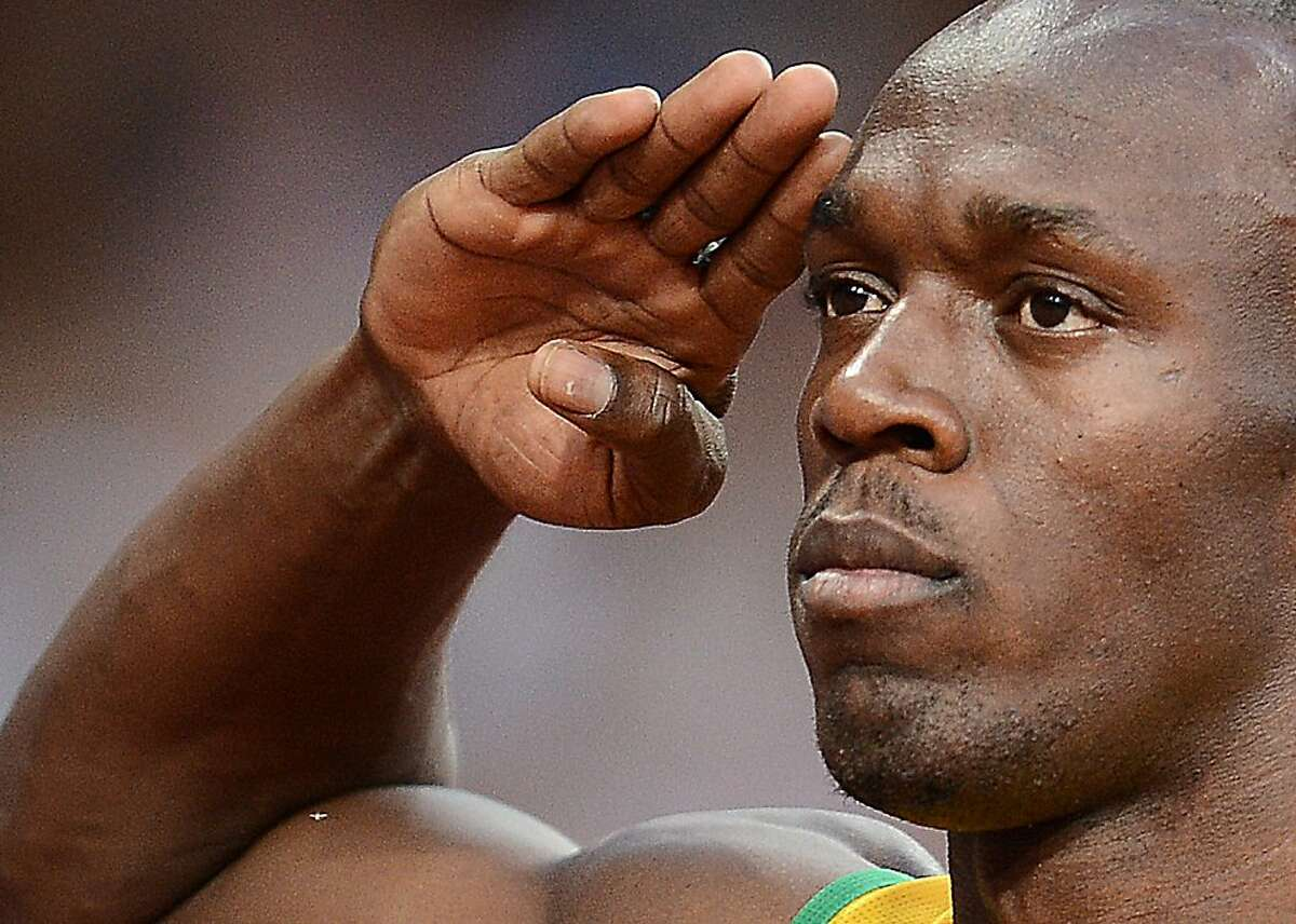 TOPSHOTS Jamaica's Usain Bolt salutes prior to competing in the men's 200m semi-finals at the athletics event of the London 2012 Olympic Games on August 8, 2012 in London. AFP PHOTO / FRANCK FIFEFRANCK FIFE/AFP/GettyImages