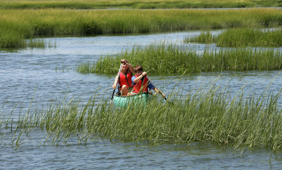Connecticut Audubon Society Coastal Center naturalist Samantha Ross paddles with camper Colin Dunn, 11, of Newtown, during an outing in Milford on Monday August, 6, 2012. The center holds several  guided canoe outings for families in the Charles E. Wheeler Salt Marsh. Photo: Unknown, B.K. Angeletti / Connecticut Post freelance B.K. Angeletti