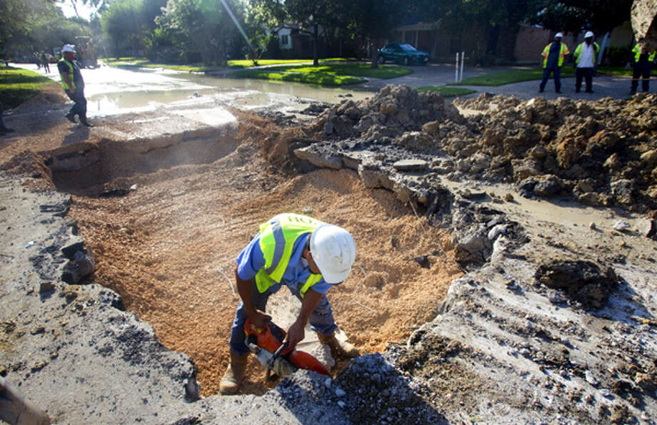 Crews work to repair a water pipe that busted in the 8000 block of Richmond Avenue Thursday, Aug. 9, 2012, in Houston. Photo: .