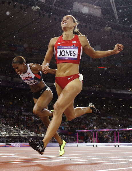 LoLo Jones, right, crosses the finish line to place fourth in the women's 100-meter hurdles final du