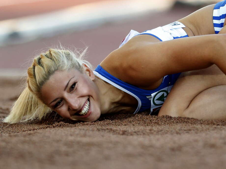 Greece's Voula Papachristou lands in the sand after her jump at the Women's Triple Jump final at the European Athletics Championships in Helsinki, Finland. The Hellenic Olympic Committee removed Papachristou from Greece's 2012 Olympic team over comments she made on Twitter making fun of African immigrants and expressing support for a far-right party. For better and for worse, the 2012 Olympics are being shaped, shaken and indisputably changed by social media sites such as Twitter, whose immediacy and public nature has added a new and chaotic element to the Games. (AP Photo/Matt Dunham, June 29, 2012). Photo: