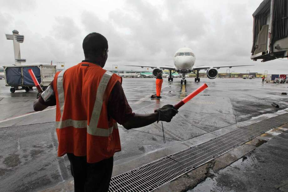 In this Wednesday, Aug. 1 2012 photo, a Delta Air Lines ramp agent assists a pilot as he pulls into a gate at JFK International airport in New York.  Travelers still have to put up with packed planes, rising fees and unpredictable security lines, but they are missing fewer business meetings or chances to tuck their kids into bed. Nearly 84 percent of domestic flights arrived within 15 minutes of their schedule time in the first half of the year, the best performance since the government started tracking such data in 1988. (AP Photo/Mary Altaffer) Photo: Mary Altaffer