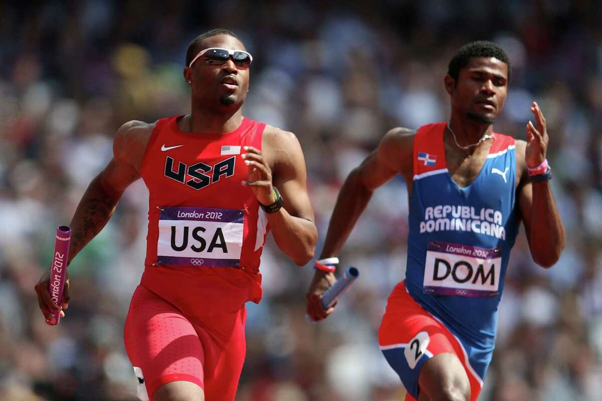 : Manteo Mitchell of the United States and Gustavo Cuesta of Dominican Republic compete during the Men's 4 x 400m Relay Round 1 heats on Day 13 of the London 2012 Olympic Games at Olympic Stadium on Thursday in London, England.