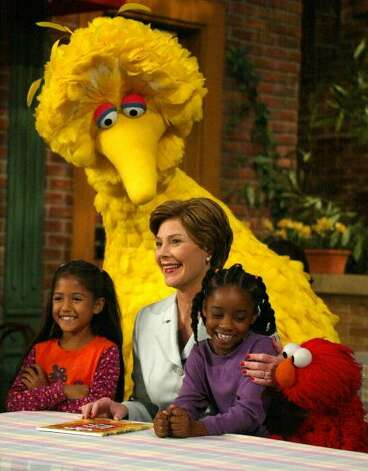 "File: First Lady Laura Bush laughs with Big Bird (C) and Elmo (R) September 19, 2002 while taping a show of Sesame Street in New York.  The children, Sydney Martines (L) and Sienna Jefferies (2nd R), read a book with Mrs. Bush for the show ""Reading Fundamentals: Books, and Cultural Appreciation.""         (Photo credit should read DON EMMERT/Getty Images) (AFP/Getty Images)"