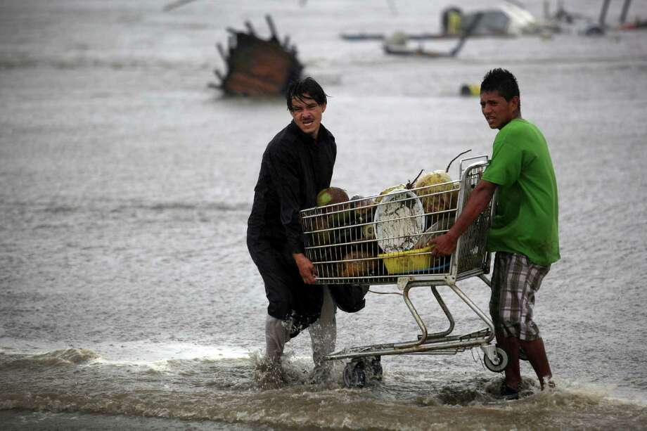Coconut vendors try to recover their goods after they were caught unprepared when high waves dragged their beach stalls into the sea in Veracruz, Mexico, Thursday, Aug. 9, 2012.  Tropical Storm Ernesto headed into Mexico's southern Gulf coast as authorities in the flood-prone region prepared shelters, army troops and rescue personnel for drenching rains. (AP Photo/Felix Marquez) Photo: Felix Marquez, Associated Press / AP