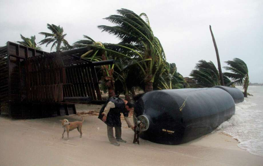 A man inspects marine fenders that were ripped from the docks and dragged to the beach after Hurricane Ernesto made landfall overnight in Mahahual, near Chetumal, Mexico, Wednesday, Aug. 8, 2012. Marine fenders are used to prevent naval vessels from colliding against each other or against docks, wharves and piers. (AP Photo/Israel Leal) Photo: Israel Leal, Associated Press / AP