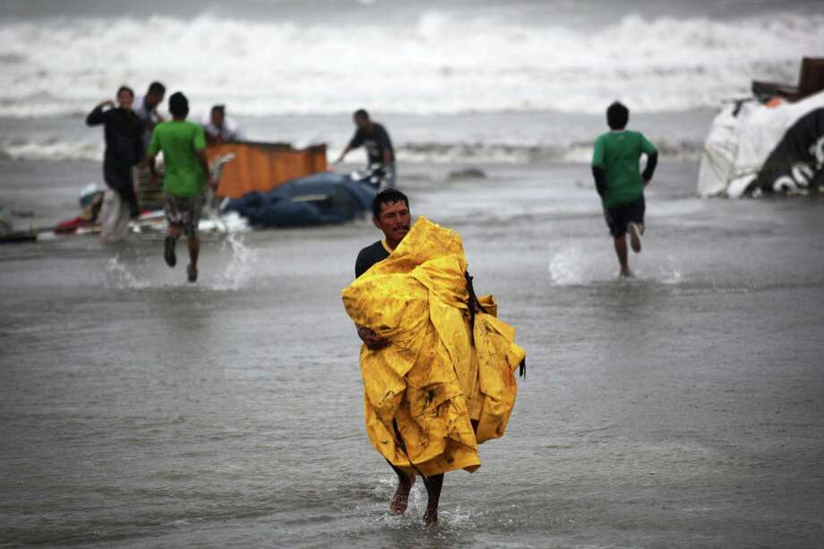 A vendor recovers a plastic tarp after vendors were caught unprepared when high waves dragged their beach stalls into the sea in Veracruz, Mexico, Thursday, Aug. 9, 2012. Tropical Storm Ernesto headed into Mexico's southern Gulf coast as authorities in the flood-prone region prepared shelters, army troops and rescue personnel for drenching rains. (AP Photo/Felix Marquez) Photo: Felix Marquez, Associated Press / AP