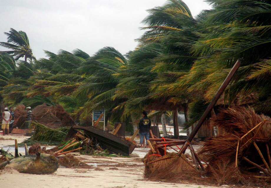 People survey the damage caused by Hurricane Ernesto after it made landfall overnight in Mahahual, near Chetumal, Mexico, Wednesday, Aug. 8, 2012. (AP Photo/Israel Leal) Photo: Israel Leal, Associated Press / AP