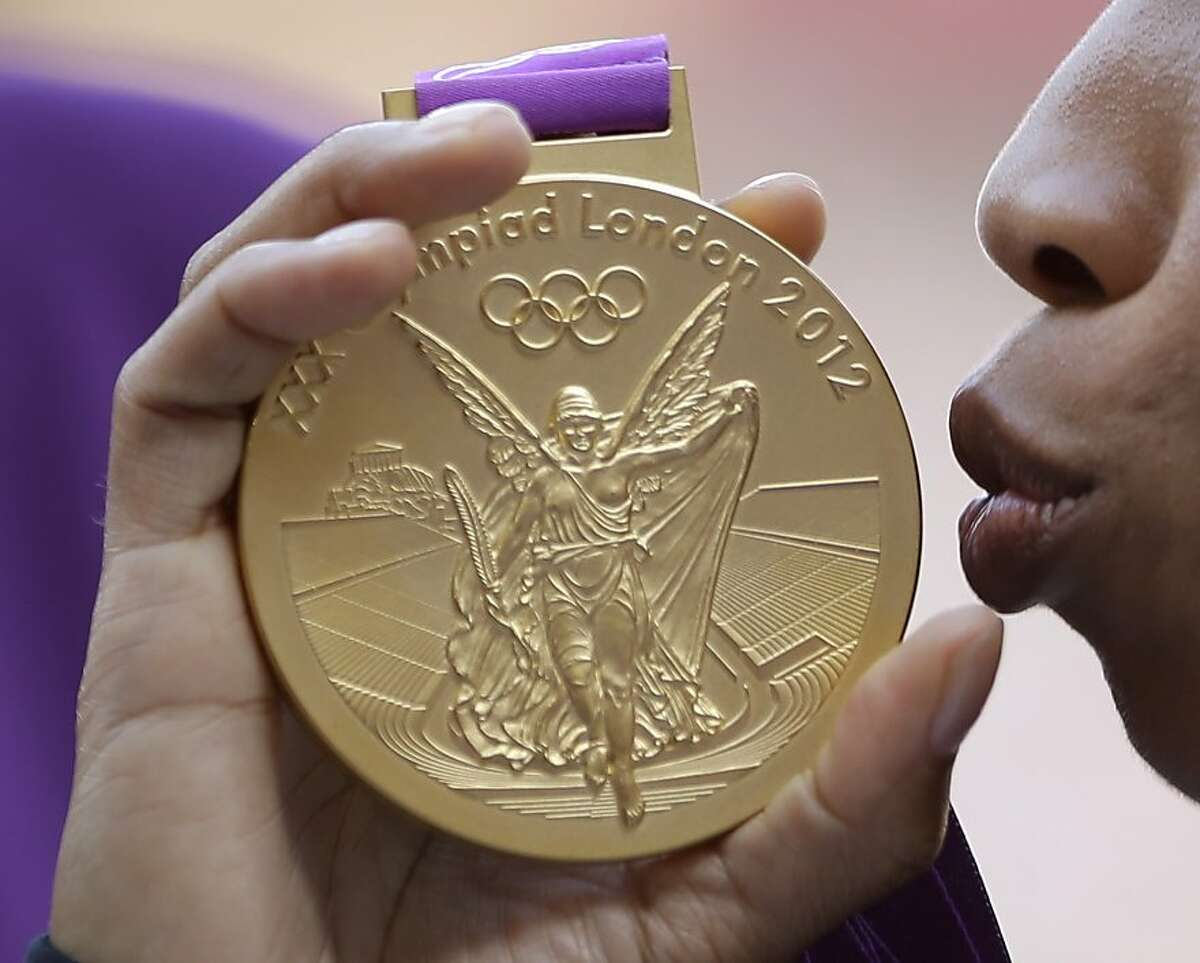 United States' Allyson Felix kisses the gold medal for the women's 200-meter during a ceremony at the athletics in the Olympic Stadium at the 2012 Summer Olympics, London, Thursday, Aug. 9, 2012. (AP Photo/Matt Slocum)