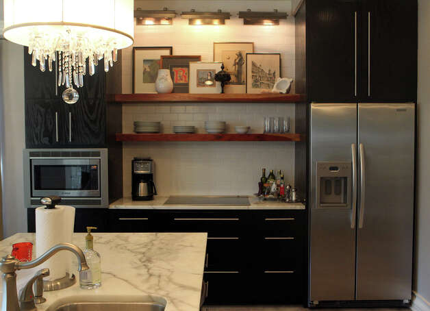 Stainless appliances, black cabinetry and marble countertops frame shelving used for utilitarian and decorative purposes in the kitchen of Tamara and Jason Riggan. (Monday August 6, 2012) John Davenport©John Davenport/San Antonio Express-News Photo: John Davenport, San Antonio Express-News / John Davenport/©San Antonio Exp