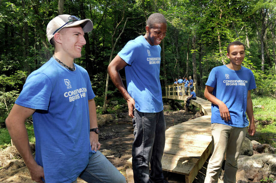 From left, Mike Dibble, 19; Ehi Osagie, 17 and Alessandro Da Silva, 17, talk about their work building a trail and a bridge on the Ives Trail section that runs through property near Long Ridge Road in Danbury, Thursday, Aug. 9, 2012. The boys were part of a crew under the direction of the Student Conservation Association and Myor Mark Boughton's teen summer employment program. Photo: Carol Kaliff / The News-Times