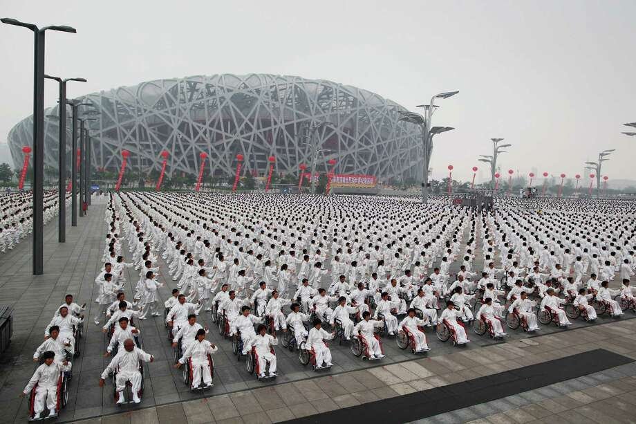 "Time for some exercise, starting with these 33,996 tai chi practitioners setting a new record outside the ""Bird's Nest"" National Olympic Stadium on August 8, 2009 in Beijing. Photo: Feng Li, Getty Images"