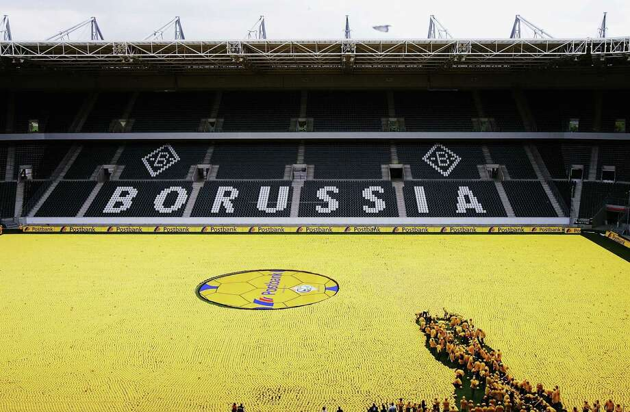 Lots of volunteers were needed to cover the Borussia Moenchengladbach soccer pitch with 142,000 balls, setting a new Guiness World Record, on June 6, 2005 in Monchengladbach, Germany. Photo: Christof Koepsel, Bongarts/Getty Images / k