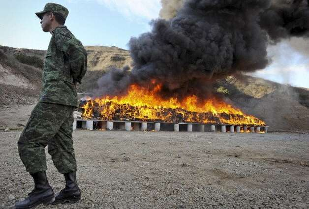File: In this file photo a Mexican soldier walks in front of bundles of seized marijuana being incinerated at a military base in Tijuana, Mexico, on Wednesday, Oct. 20, 2010. Authorities had carried out the biggest marijuana bust in Mexico's history that week, when approximately 134 tons of marijuana headed for the U.S. were confiscated by soldiers and police. Mexico has impounded more than 7,400 tons of marijuana that year as part of President Felipe Calderon's fight against drug cartels. Photographer: David Maung/Bloomberg via Getty Images (Bloomberg via Getty Images)