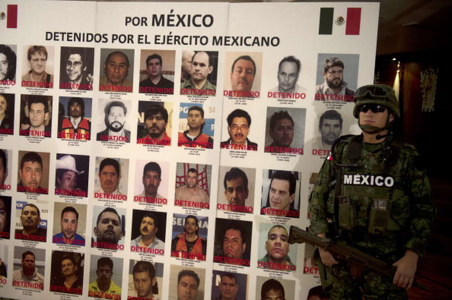 File: In this file photo a Mexican army soldier stands guard beside board with pictures of alleged drug cartels members already arrested. Photo YURI CORTEZ/AFP/GettyImages) (AFP/Getty Images)
