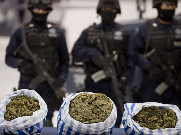 "File: Members of the Federal Police escort three sacks of Marijuana from the drug cartel ""Independiente de Acapulco."" More than 40.000 people have been killed in rising drug-related violence in Mexico since December 2006, when President Felipe Calderon deployed soldiers and federal police to take on organized crime. (Photo ALFREDO ESTRELLA/Getty Images) (AFP/Getty Images)"